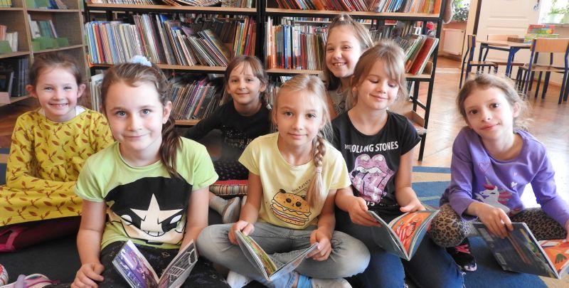 Grupa dzieci na tle regałów bibliotecznych z książkami w dłoniach