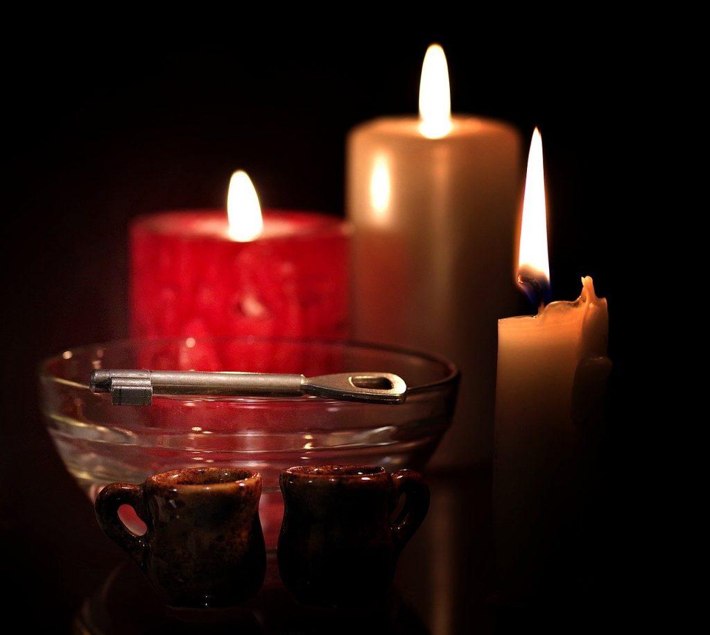 Ilustracja andrzejek - w tle trzy kolorowe palące się świece, przed nimi szklana misa, na której leży klucz, przed misą dwa małe gliniane kubeczki.