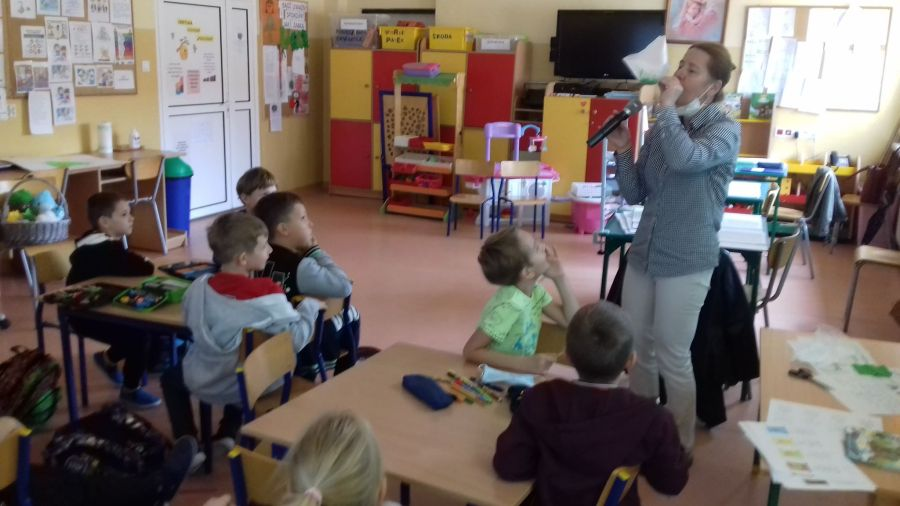 Dzieci obserwują eksperyment z powietrzem w foliowym woreczku prowadzony przez nauczyciela.