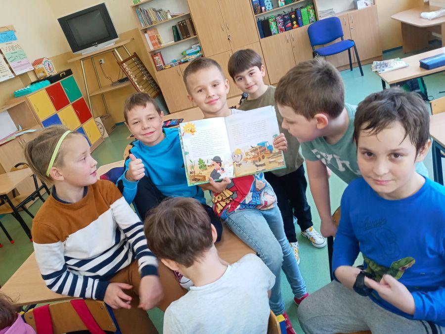 Uczniowie klasy IId czytają książkę o przygodach Fajniaków.