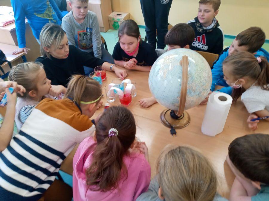 Wychowawca kl.IId z uczniami przeprowadza eksperyment o przenikaniu wody przez bibułę do szklanek.