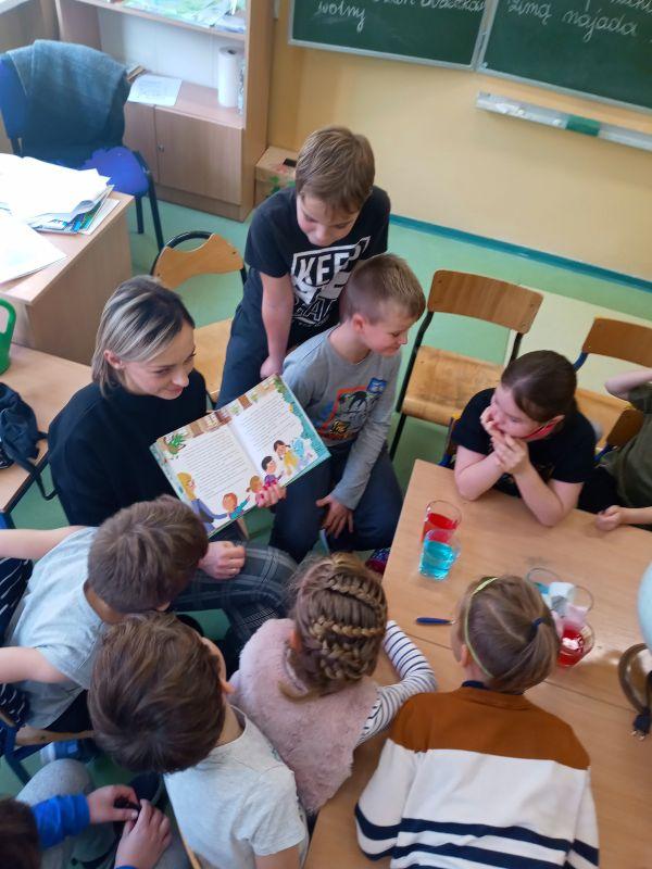 Wychowawca klasy IId prezentuje dzieciom opowiadanie o przygodach Fajniaków, na ławce eksponaty do przeprowadzenia eksperymentów o wodzie.