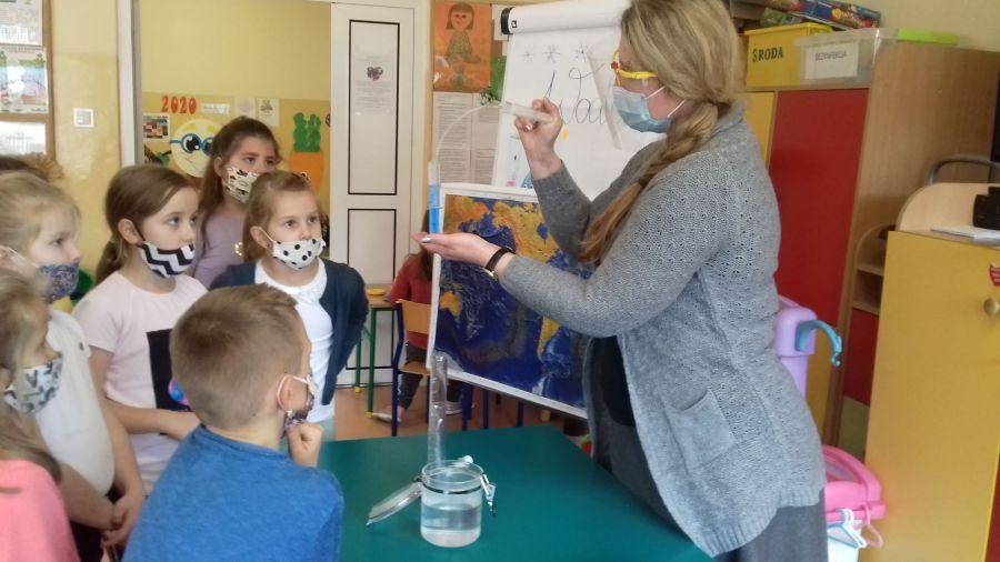 Żywioł Woda-nauczyciel prezentuje dzieciom eksperyment z wodą wykonany dwoma strzykawkami