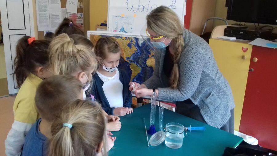 Żywioł woda-nauczyciel przedstawia dzieciom eksperyment z wodą w strzykawce