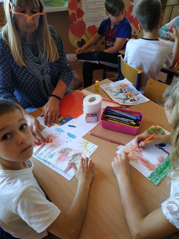Dzieci pod opieką nauczyciela wykonują prace plastyczne do Żywiołu Ogień.