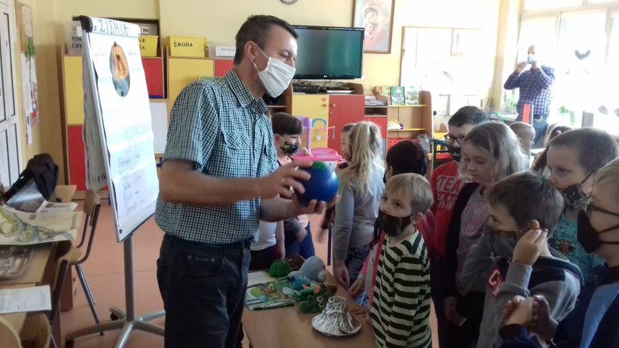 Nauczyciel prezentuje dzieciom budowę ziemi na eksponacie-Żywioł Ziemia