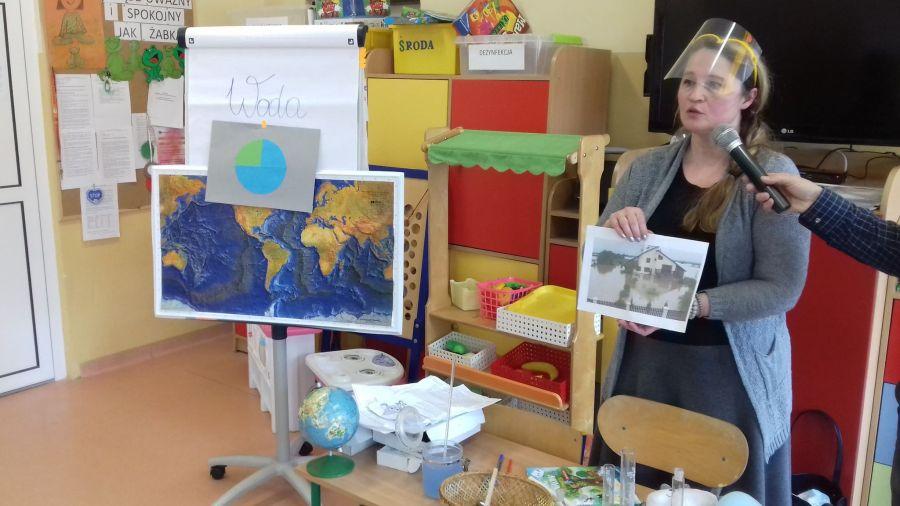 Nauczyciel prezentuje Żywioł Wody jako niebezpieczeństwo powodzi-zdjęcie powodzi w Połańcu sprzed kilku lat.