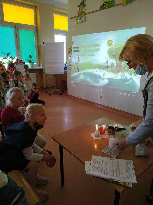 Nauczyciel przedstawia dzieciom eksperyment z Żywiołu Ogień- spalanie, w tle prezentacja multimedialna o Fajniakach.