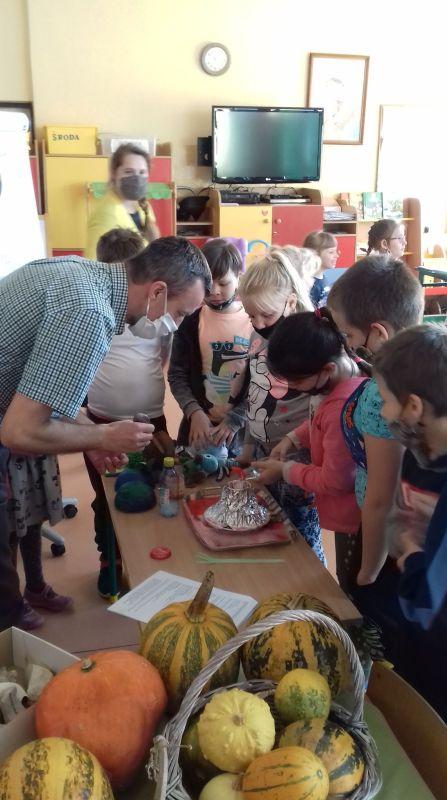 Nauczyciel przedstawia dzieciom eksperyment z Żywiołu Ziemia-wybuch wulkanu, w tle wystawa dyni.