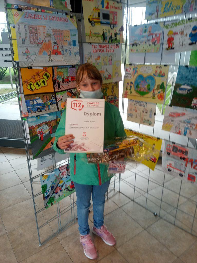 Uczennica trzymająca w ręku dyplom oraz nagrody za wyróżnienie w konkursie.